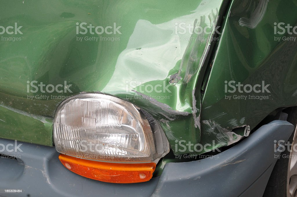 Damaged front of green car with headlight royalty-free stock photo