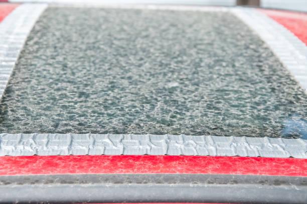 beschädigte glas-dach-fenster oder schiebedach auf das rote auto, verklebt mit klebeband zu verhindern, dass wasser in das innere des fahrzeugs zu kommen - auto trennwand stock-fotos und bilder
