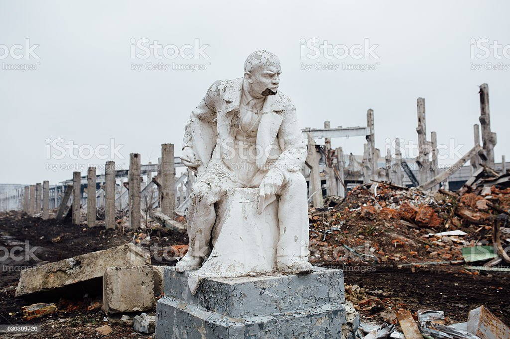Damaged Lenin statue sitting on a chair with  book in stock photo
