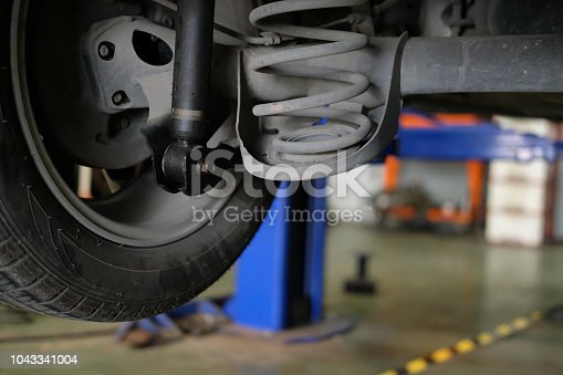 damaged rear car shock absorber & spring in auto service repair garage