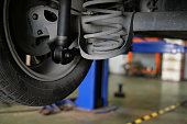 damaged rear car shock absorber & spring in auto service repair garage