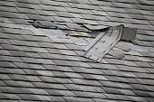 A badly damaged roof with missing shingles in need of repair