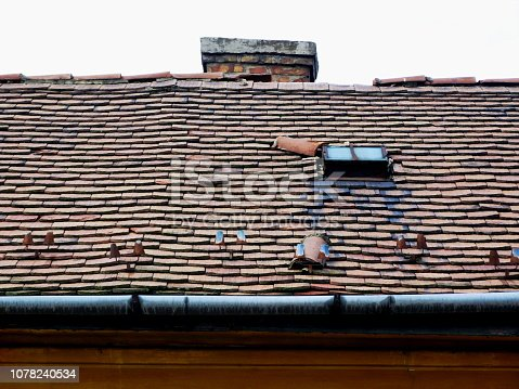 damaged sloped clay roof with decaying and breaking clay roof tiles, brick chimney and old galvanized steel gutter eavestrough