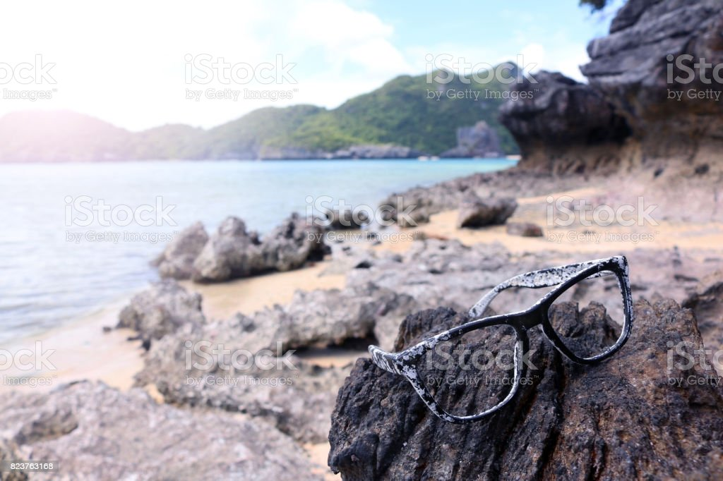 Damaged sunglasses on the rocks on the beach. stock photo
