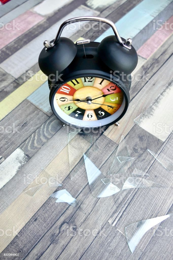 Damaged vintage colorful alarm clock, glass lying on wooden floor stock photo
