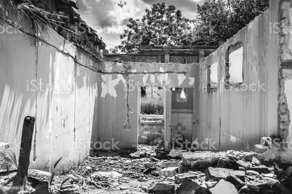 Uszkodzona ściana domowego domu cywilnego lub budynku z dziurą i zawalonym dachem zniszczonym przez granat w strefie wojny po bombardowaniu terrorystów - Zbiór zdjęć royalty-free (Bieda - Problem społeczny)