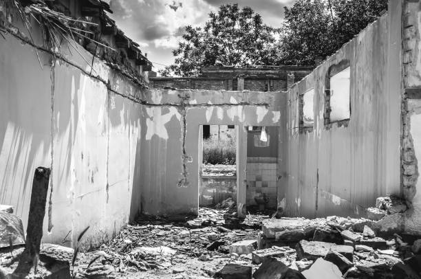 pared dañada de la casa civil doméstica o edificio con agujero y derrumbado techo destruidos por granadas en la zona de guerra después de bombardeos terroristas - antigua yugoslavia fotografías e imágenes de stock
