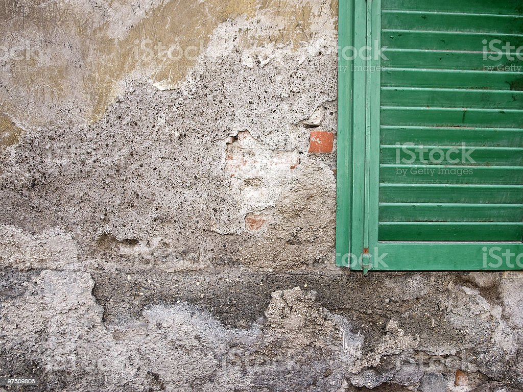 damaged wall with vibrant green window royalty-free stock photo