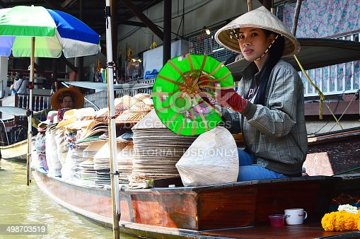 Bangkok, Thailand - November 4, 2013: Unknown saleswoman who sells directly from the boat, a traditional Thai at Damnoen Saduak Floating Market, the most popular floating market in Thailand.