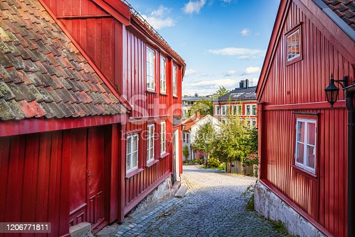 Red woodenhouses in old town village in Damstredet Cobblestone Street in Oslo under blue summer sky. One of the oldest streets in the historic center of Oslo, Capital of Norway. Damstredet, Oslo, Norway, Scandinavia