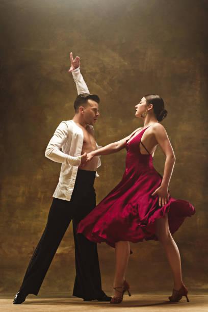 dance ballroom couple in red dress dancing on studio background - tango taniec zdjęcia i obrazy z banku zdjęć