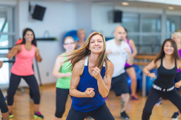 Dance fitness A woman in a dance workout class smiles at the camera. They are all in sportswear and moving to the side. exercise class stock pictures, royalty-free photos & images