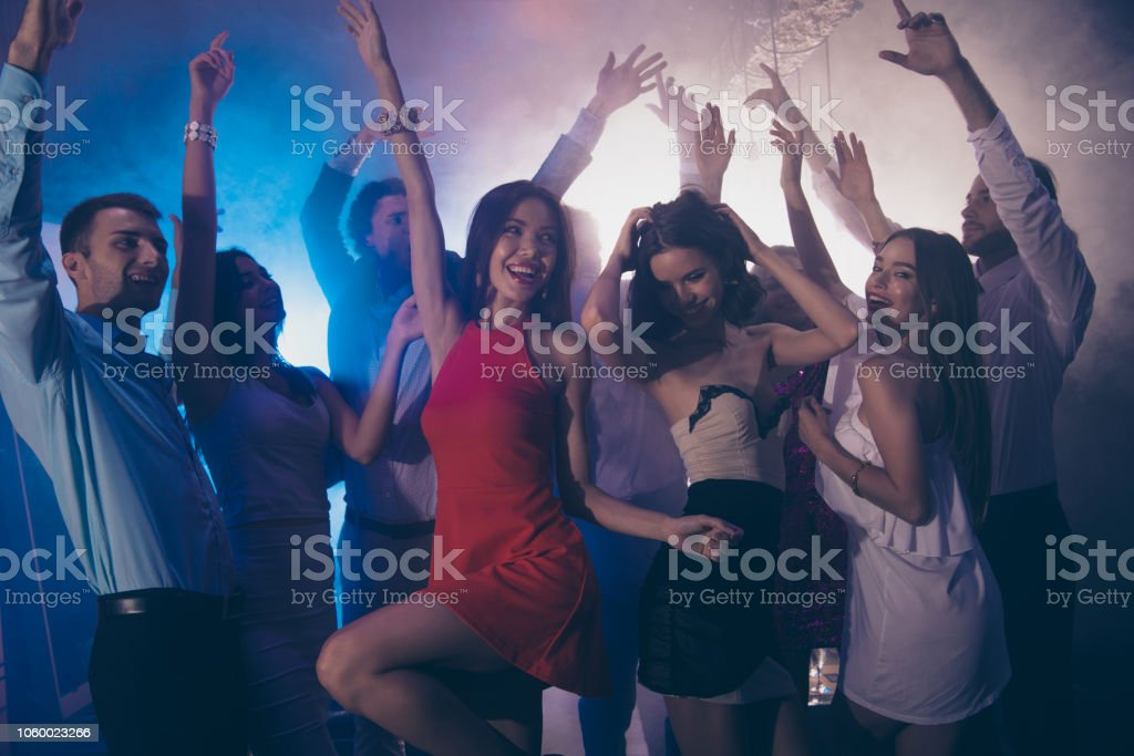 Dance floor. Many attractive people dance on the floor raised hands...