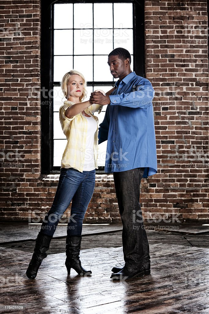 Dance lesson: young biracial couple dancing in an abandoned warehouse stock photo
