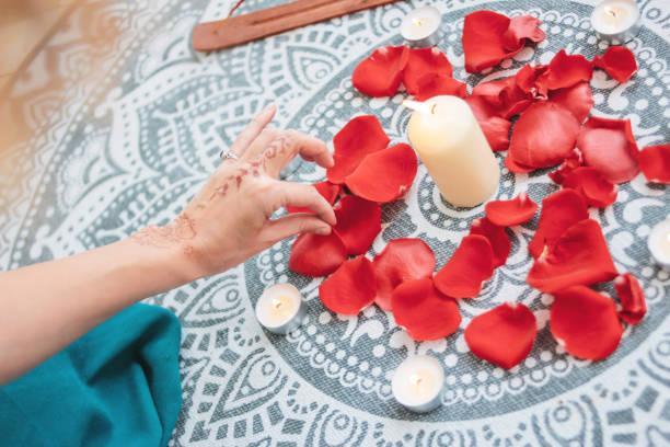 dance of female hands with mehendi over the altar of candles and rose petals, women practices - mão no chakras velas imagens e fotografias de stock