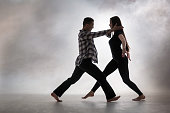 Attractive pair of dancers are performing modern dance. Slender young woman dancer dressed in a black T-shirt and black leggings. Athletic young man dancer wearing a plaid shirt and black sweatpants. Studio shooting on a light background in a light haze