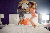 Cute kids elementary age 5 and 7 dance and jump and act silly on the bed of a hotel room in Key West Florida. Happy siblings on vacation fully enjoying the freedom and adventure