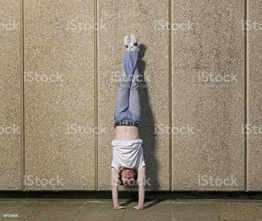 Dancer doing handstand against wall royaltyfri bildbanksbilder