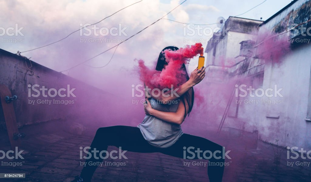 Chica bailarina en azotea usando bomba de humo rosa - foto de stock