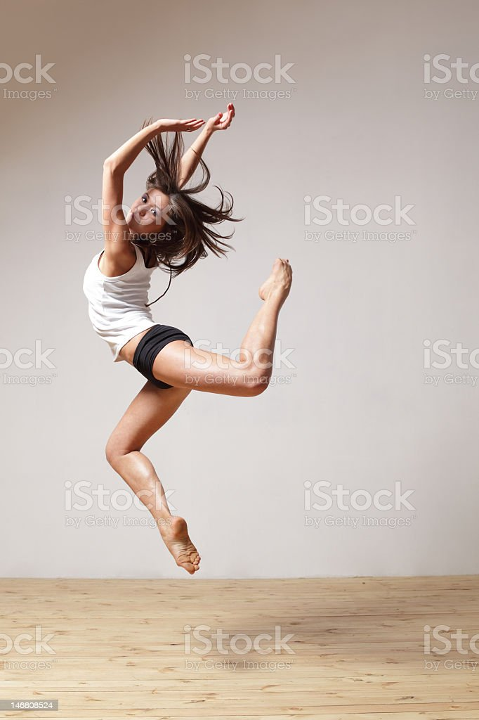 Dancer in mid-air wearing a white tank top and black shorts stock photo