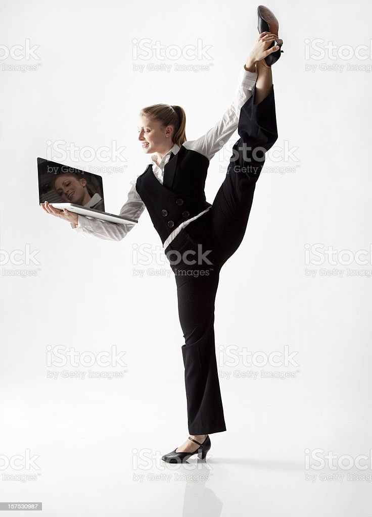 dancer stretching her leg with one hand, holding laptop royalty-free stock photo