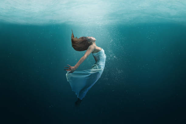 Dancer underwater in a state of peaceful levitation stock photo