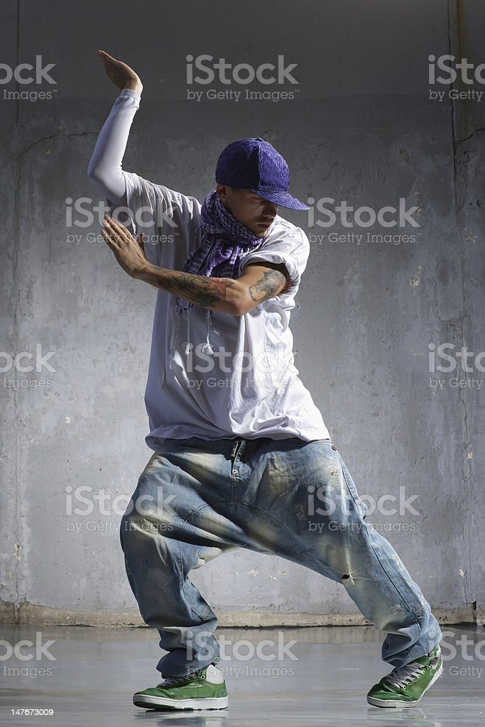 Dancer wearing violet snapback and loose clothes near wall royalty-free stock photo