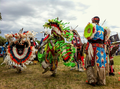 Horizontal closeup of a line of male dancers dressed in ornate, traditional clothing, dancing to the drums at the annual Taos Pow-Wow, New Mexico