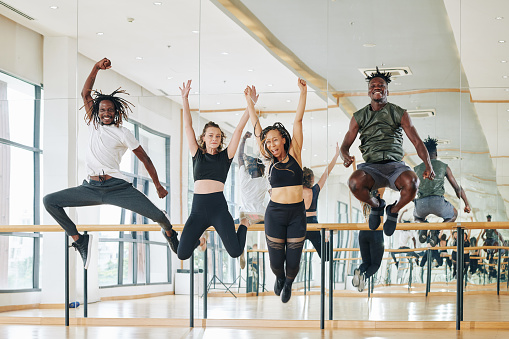 Multi-ethnic group of happy dancers jumping from excitement after productive training