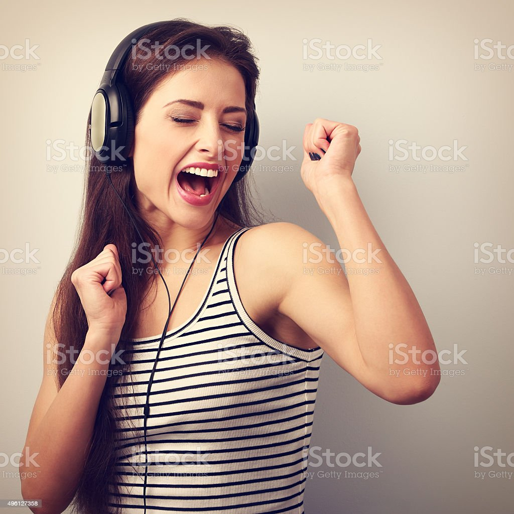 Dancing active young woman in headphones singing the song stock photo