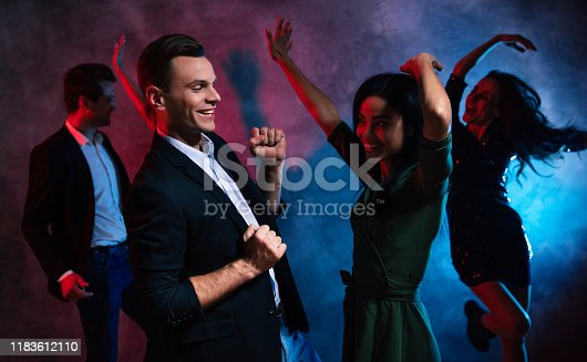 497317250 istock photo Dancing all night long. Handsome man is a smart outfit is looking and the cute African-American girl in a green dress, while they are both dancing at the party. 1183612110