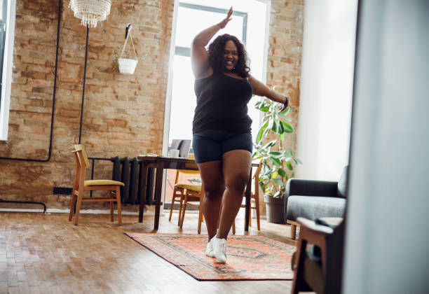 Dancing alone always makes me happy stock photo Happy woman with excess weight smiling and dancing alone in sports clothes exercising stock pictures, royalty-free photos & images