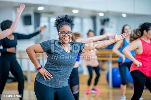 A woman of african descent looks into the camera smiling while she dances during a fitness class. She has one hand on her hip and the other arm extended out fully.