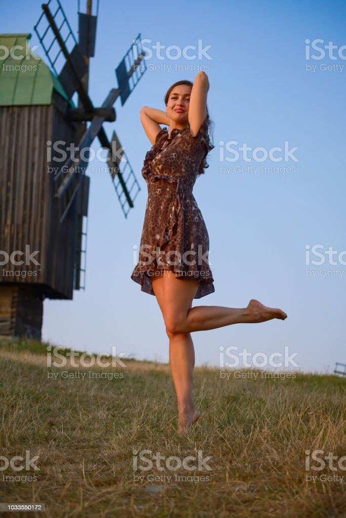 Dancing beautiful girl field and windmill stock photo