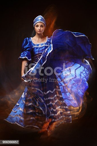 181894581 istock photo A dancing beautiful woman in a blue traditional African suit on a black background with mixed light. 956366652