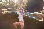 A little girl is dancing in the back garden with a giant bubble wand