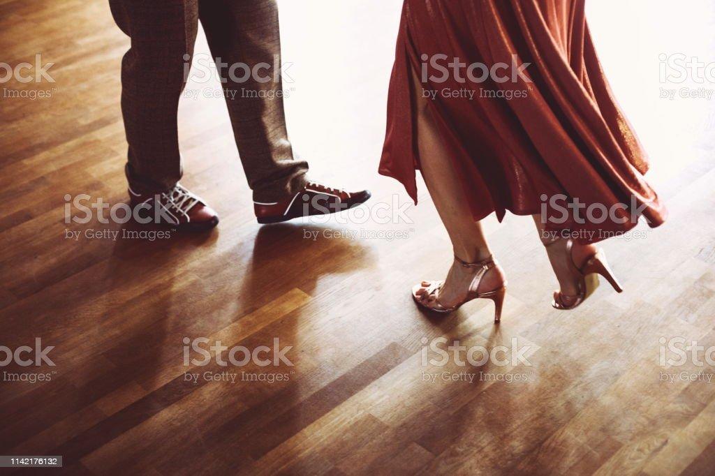 Dancing couple in the light dance hall of dance school