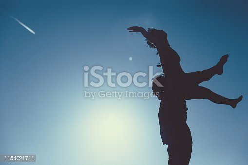 Silhouette of a dance figure of a man holding a woman in the air with legs and arms raised up.