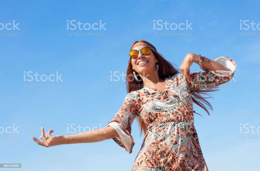 Dancing hippie girl with copy space in blue sky outdoor in summer - Photo