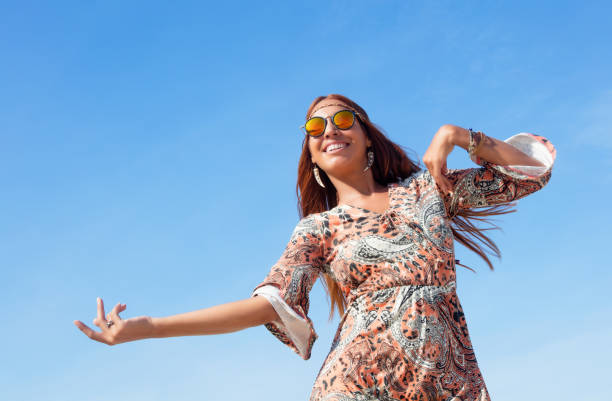 Dancing hippie girl with copy space in blue sky outdoor in summer stock photo