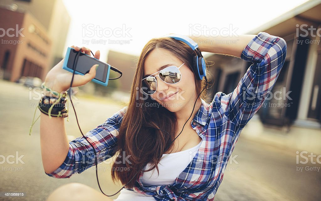 Dancing hipster girl with headphones in city during summer stock photo