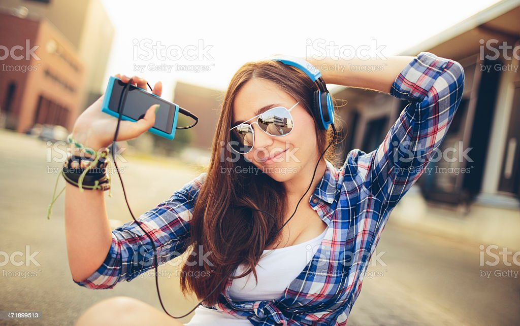Dancing hipster girl with headphones in city during summer royalty-free stock photo