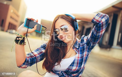 istock Dancing hipster girl with headphones in city during summer 471899513
