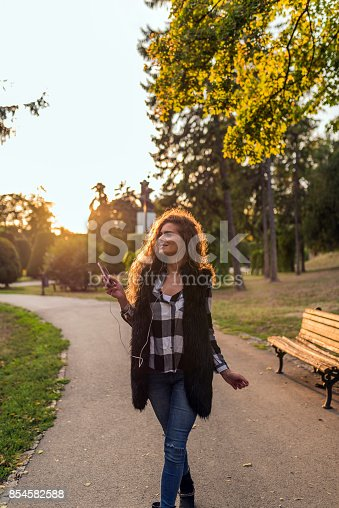 625928750 istock photo Dancing hipster girl with headphones in city during summer 854582588