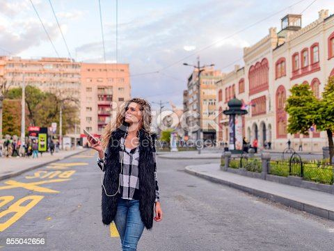 istock Dancing hipster girl with headphones in city during summer 855042656