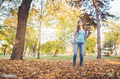 Young, smiling, woman with headphones on, listening to the music in a public park. On a beautiful autumn day.