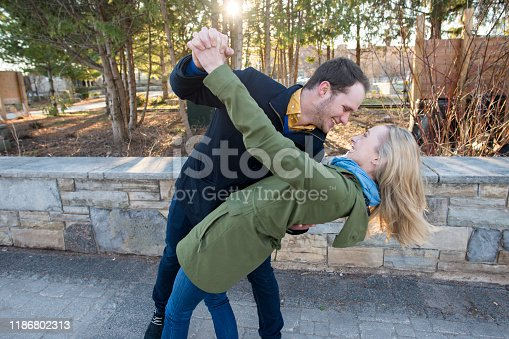 Happy young Caucasian couple having fun dancing in a public park on a sunny spring day. They are laughing as the young man dips the blonde young woman backwards.
