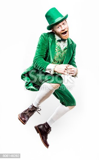 A portrait of a stereotypical Irish character doing a dance to celebrate Saint Patricks day.  He smiles, jumping into the air with both feet off the ground.  Isolated on white studio background.
