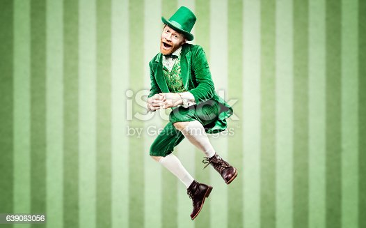 A stereotypical Irish character all ready for Saint Patricks day.  He dances, jumping high in the air during a jig with a big smile on his face.  Studio portrait.  Horizontal image with copy space.  Green striped wallpaper background.