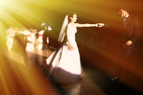 Dancing newlyweds Newlyweds dancing with wedding party in sunshine rays. sun shining through dresses stock pictures, royalty-free photos & images